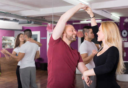 Group of cheerful happy young adults dancing salsa in club Stock Photo