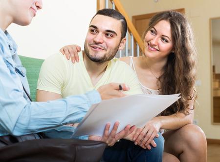 empleada domestica: Pareja positiva joven y agente de bienes raíces de firmar un acuerdo en el hogar