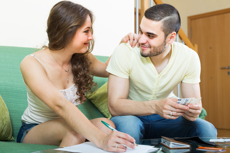 calculated: Happy young couple calculating the family budget at home