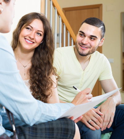 private insurance: Positive young couple discussing details of private insurance with agent