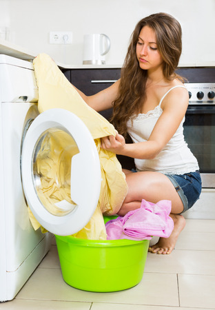 bad hygiene: Home laundry. Sad girl with clothes near washing machine at home Stock Photo
