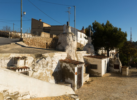 chinchilla: Dwellings caves  with сhimneys  into rock. Chinchilla, Albacete, Spain Stock Photo