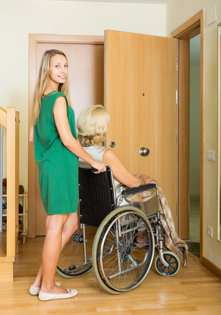 threshold: woman in wheelchair with young assistant at threshold