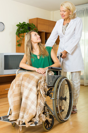 incapacitated: Happy elderly doctor visiting handicapped young girl at home
