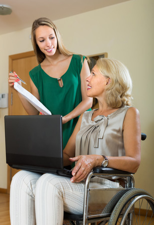 incapacitated: Female social worker with laptop questioning handicapped aged woman. Focus on mature
