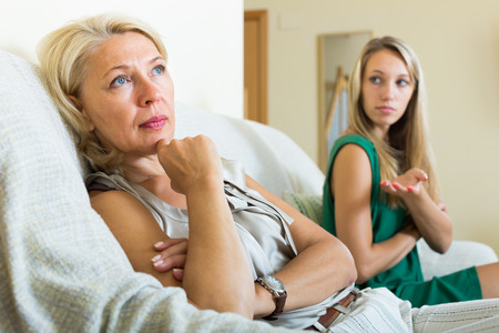 fracas: adult daughter  and  sad mature mother having conflict on sofa