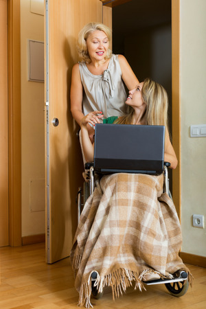 incapacitated: Happy woman in wheelchair with female assistant working on laptop at home