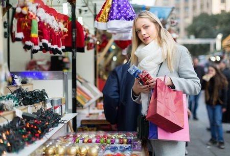 purchaser: Beautiful young long-haired woman choosing Christmas decoration at market