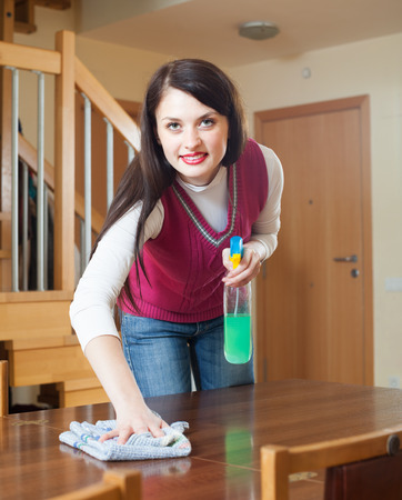 cleanser: brunette girl cleaning table with cleanser and rag