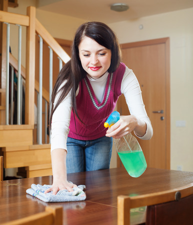 cleanser: brunette woman dusting wooden table with rag and cleanser at home