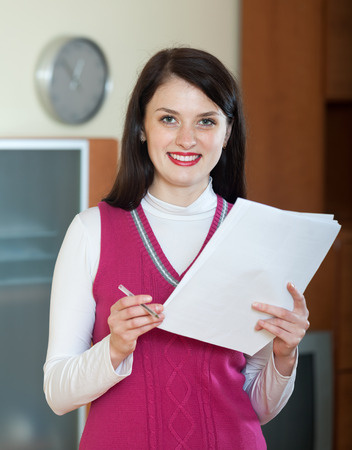 parsimony: Friendly brunette woman with financial documents at home or office interior