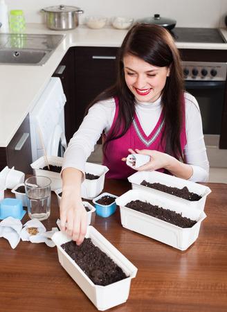 siembra: Mujer sembrando pl�ntulas en macetas en casa