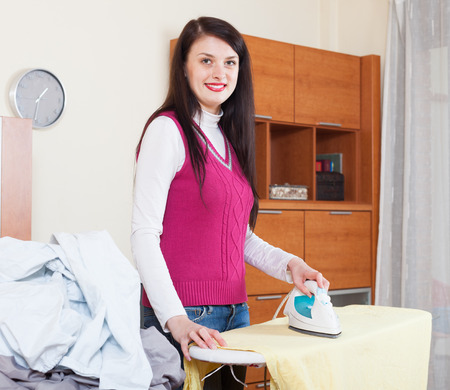 woman ironing: Smiling brunette woman ironing with iron