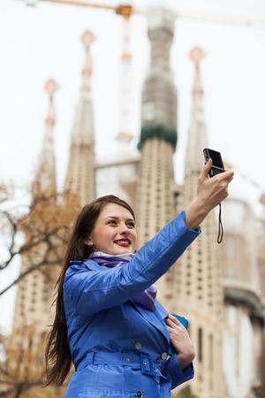 sagrada familia: Girl in coat with digital camera photographing herself against Sagrada Familia at Barcelona Editorial