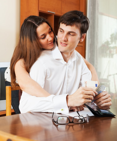 utility payments: Young couple with money and documents in home interior