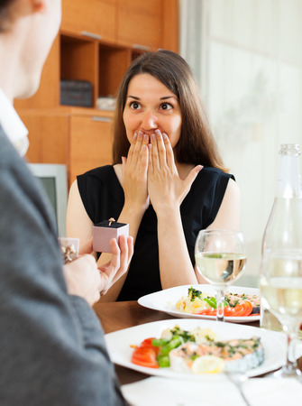 affiance: Marriage proposal. Man presenting to amazed woman engagement ring in box  at table
