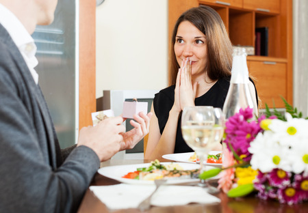 affiance: Marriage proposal. Man presenting to amazed woman engagement ring at table  in home Stock Photo