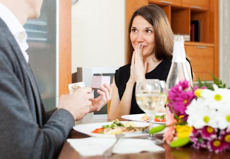 mariage: proposition de mariage. Man présenter à bague de fiançailles femme surpris à table dans la maison