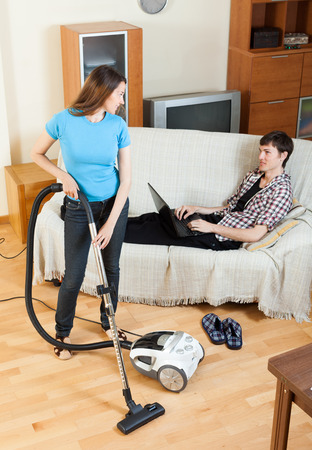 vaccuum: woman doing house cleaning with vaccuum cleaner during man resting over sofa
