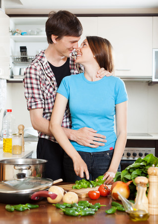 Young loving couple hugging in home kitchen photo
