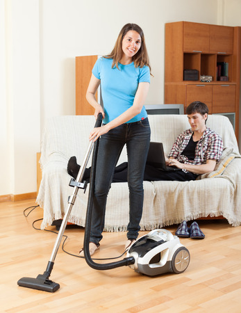 vaccuum: Young woman doing house cleaning with vaccuum cleaner during man resting over sofa