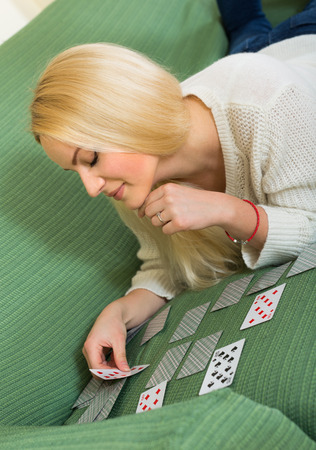 solitaire: Relaxed blonde young woman playing solitaire on sofa in home interior