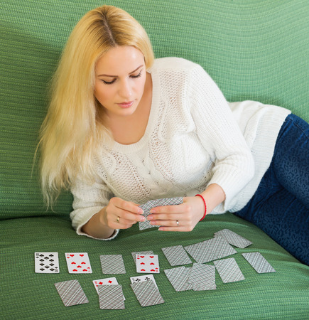 predictor: Relaxed blonde housewife on couch telling fortunes by cards indoors