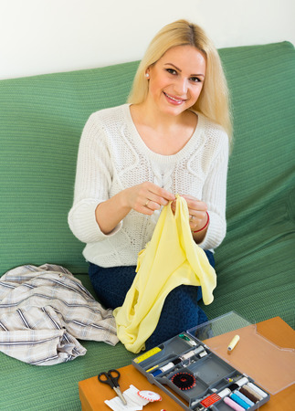 mending: Attentive blond girl on couch mending linen and smiling