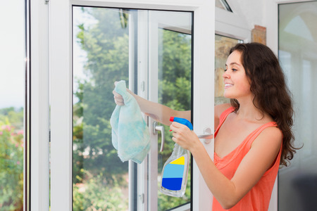 cleaning service: Long-haired woman cleaning windows with spray in home and smiling