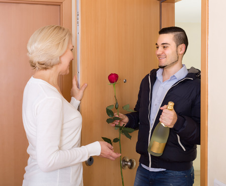 Mature woman meeting young boyfriend holding flowers and wine photo
