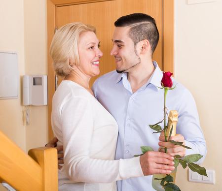 handsome man and smiling elderly woman standing at doorway