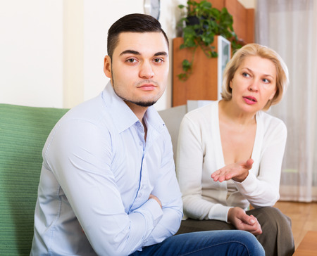offended: Mature woman explaining something to offended young man