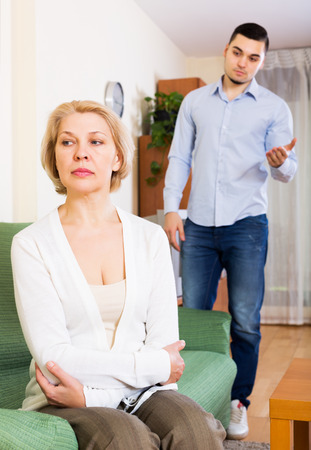 offended: Young man explaining something to offended mature woman