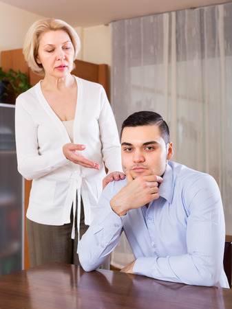 Aged woman and young boyfriend discussing something with serious faces. Focus on guy Stock Photo