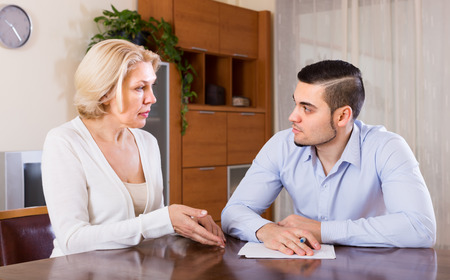 Financial crisis in family of depressed adult son and his senior mature mother Stock Photo
