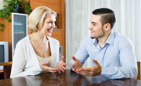 pleasant: Smiling young man and elderly woman having pleasant conversation indoor Stock Photo