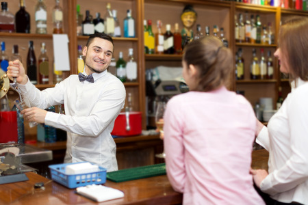 barmen: Happy young bartender and cheerful women at bar Stock Photo