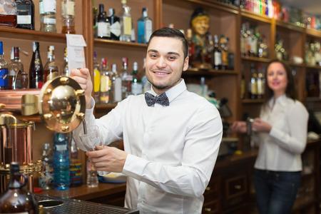 barmen: Smiling waitress and barmen working in modern bar