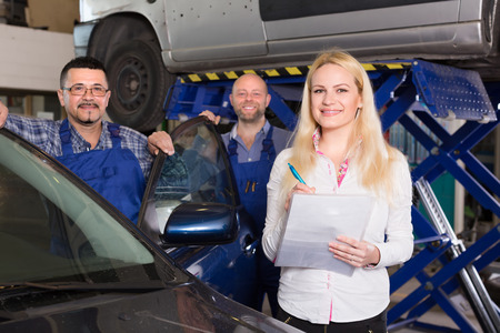 journeyman: Attractive smiling female insurance agent discussing with positive auto mechanics renewal of car Stock Photo