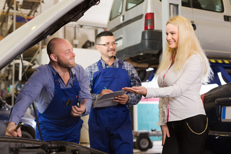 journeyman: Service crew and happy driver standing near car and smiling. Focus on man at left Stock Photo