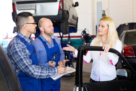 specialists: Sad girl talking with specialists at auto repair shop. Focus on the woman