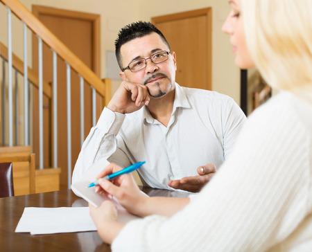 empleada domestica: Pareja llenar cuestionario para los empleados con el ordenador portátil del banco en el país