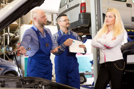 specialists: Worried young girl talking with specialists at auto repair shop. Focus on the left man