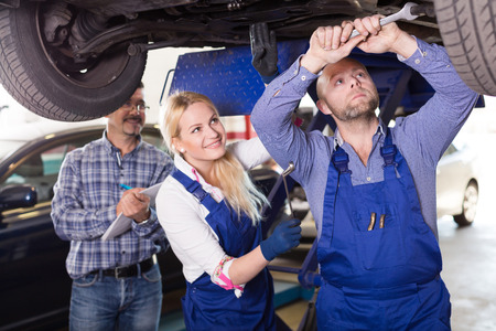 coverall: Handsome mechanic and female russian assistant working at auto repair shop Stock Photo