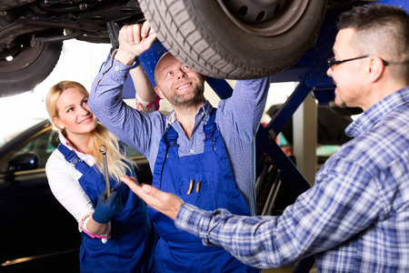 coverall: Woman and two auto mechanics Stock Photo