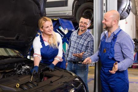 25s: Woman and two auto mechanics Stock Photo