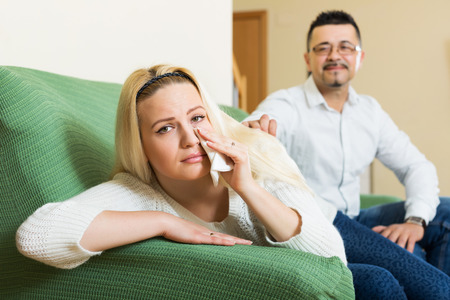 appease: Man asking for forgiveness from sad girl after quarrel at home. Focus on girl Stock Photo