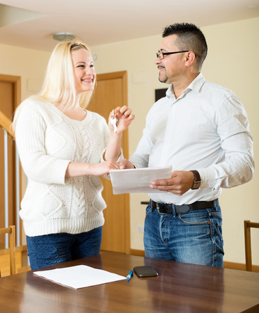 hypothec: agent giving to young girl client keys from flat and papers Stock Photo
