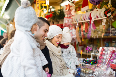 Happy young family of four at Christmas market. Selective focus on woman photo