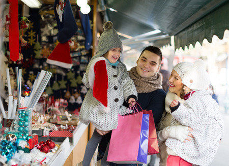 Smiling parents with kids at counter of X-mas market. Shallow depth of focus only on man photo